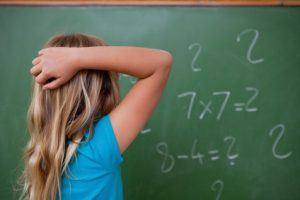 Little schoolgirl thinking while scratching the back of her head in front of a blackboard